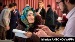An elderly woman casts her ballot at a polling station during Russia's presidential election in Moscow on March 18.