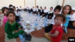A group of young Afghans wait to eat iftar, the meal traditionally taken after sunset prayers to break the fast during the Islamic holy fasting month of Ramadan, in Herat.