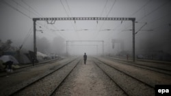 Бежанец се разхожда на влаковата линия в близост до границата между Гърция и Северна Македония през 2016 г.