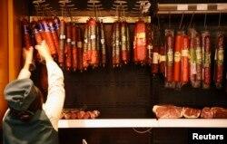 Азық-түлік дүкені жұмысшысы шұжық іліп жатыр. Ресей, Мәскеу, 19 тамыз 2014 жыл. (Көрнекі сурет)
