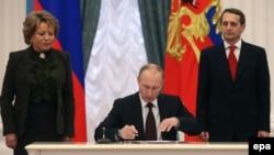 Ресей президенті Владимир Путин (ортада) Қырымды Ресейге қосу туралы заңға қол қойып отыр. Мәскеу, 21 наурыз 2014 жыл.