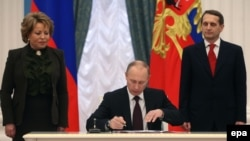 Russia -- President Vladimir Putin (C) signs a law on ratification of a treaty making Crimea part of Russia, during a ceremony in the Kremlin in Moscow, March 21, 2014