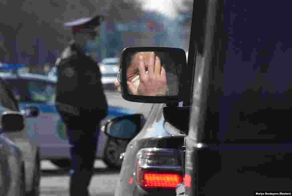 A person wearing a protective mask against the coronavirus is reflected in the side mirror of a car near a Kazakh police officer in Almaty on March 30. (Reuters/Mariya Gordeyeva)