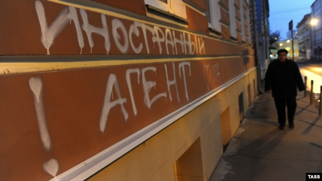 "A man walks past graffiti reading ""Foreign Agents. I Love USA"" on the building used by the Memorial human rights center in Moscow in November."