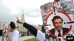 Members of a Georgian political youth group hold portraits of President Mikheil Saakashvili demanding answers about the 2008 Russia-Georgia conflict at a rally in Tbilisi in April 2009.