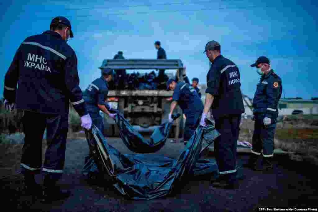 Third Prize, Spot News: Emergency workers carry the bodies of passengers on Flight MH17, which crashed near the village of Grabovo in eastern Ukraine. (Petr Shelomovskiy)