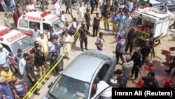 Police officers inspect a car after unidentified gunmen carried an attack on a prominent Pakistani cleric, in Karachi on March 22.