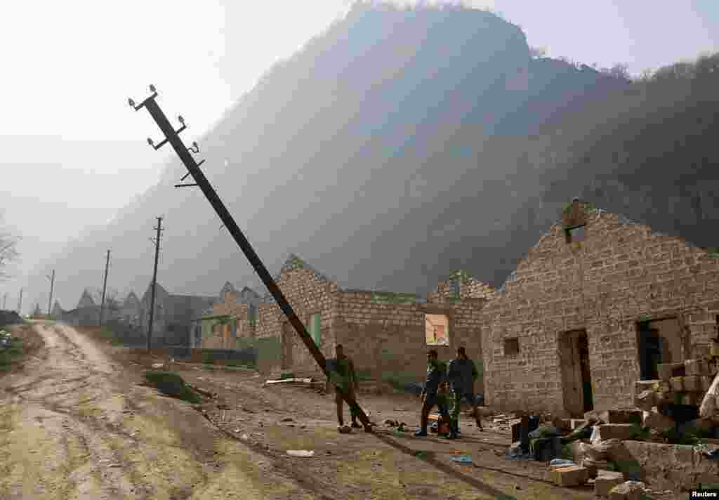 Ethnic Armenian soldiers topple a telephone pole in the village of Knaravan – a settlement recently built by ethnic Armenians in the Karvachar/Kalbacar district near Azerbaijan's border with Armenia.