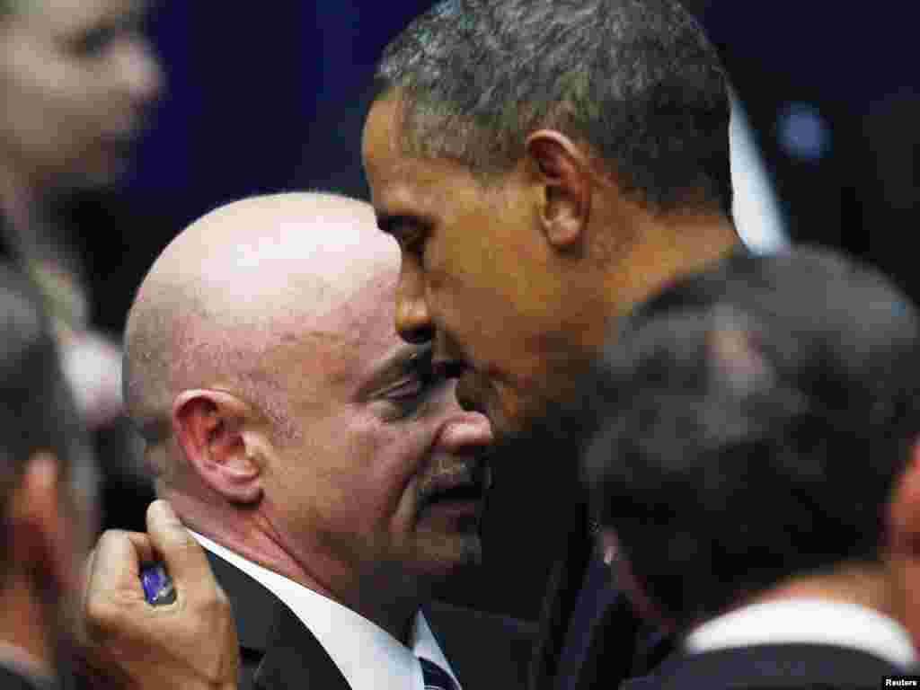 U.S. President Barack Obama hugs NASA shuttle commander Mark Kelly, the husband of U.S. Representative Gabrielle Giffords, after Giffords was seriously wounded in a shooting in Tucson, Arizona, that left six people dead. (Reuters/Jim Young)