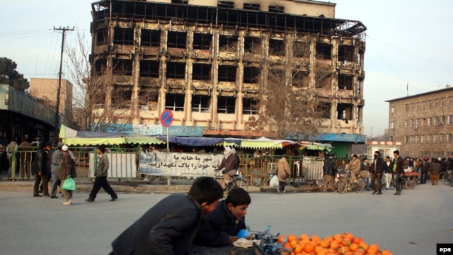 Afghans pass by a shopping mall in Kabul that was the scene of a gunbattle between Taliban militants and goverment forces a day earlier.