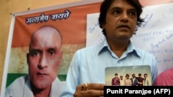 FILE: Indian friends of Kulbhushan Jadhav hold a photograph of them with Jadhav in the neighborhood where he grew up in Mumbai.