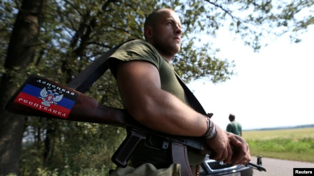 "A pro-Russian separatist showing the ""People's Republic of Donetsk"" insignia guards a checkpoint near the village of Rozsypne on August 4."