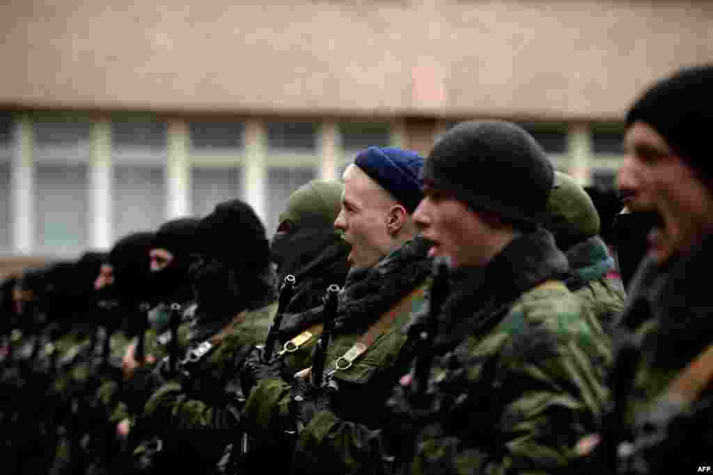 "Pro-Russian forces dubbed the ""military forces of the autonomous republic of Crimea"" attend their swearing-in ceremony in Simferopol on March 10. (AFP/Filippo Monteforte)"