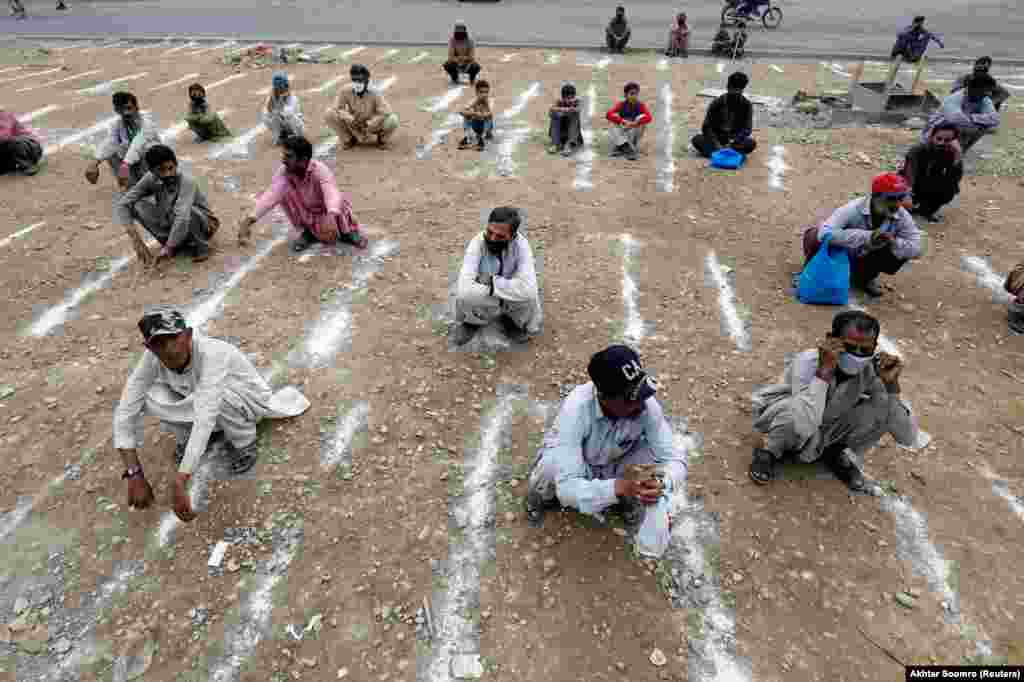 In the Pakistani city of Karachi, chalk lines are used to keep people at a safe distance. These men wait to receive sacks of food from a charity on March 26. Pakistan has shut all markets, public places, and discouraged large gatherings to contain the spread of the coronavirus.