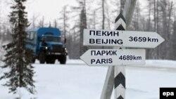 Фургон едет по зимней дороге в Сибири на фоне указателя расстояний до Пекина и Парижа. Новый Уренгой, 18 декабря 2007 года.