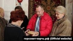 Депутат горсовета Керчи Вадим Кутузов вручает хлеб блокаднице