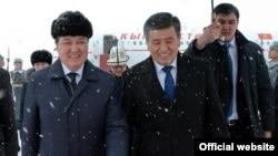Қырғызстан президенті Сооронбай Жээнбеков (ортада) әуежайда өзін күтіп алған Қазақстан премьер-министрінің бірінші орынбасары Асқар Мәминмен (сол жақта) кетіп барады. Астана, 25 желтоқсан 2017 жыл.