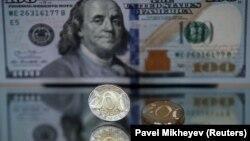 Монеты номинало 200 тенге на фоне 100-долларовой банкноты. Иллюстративное фото.