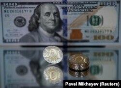 Монета 200 тенге на фоне 100-долларовой купюры. Иллюстративное фото.