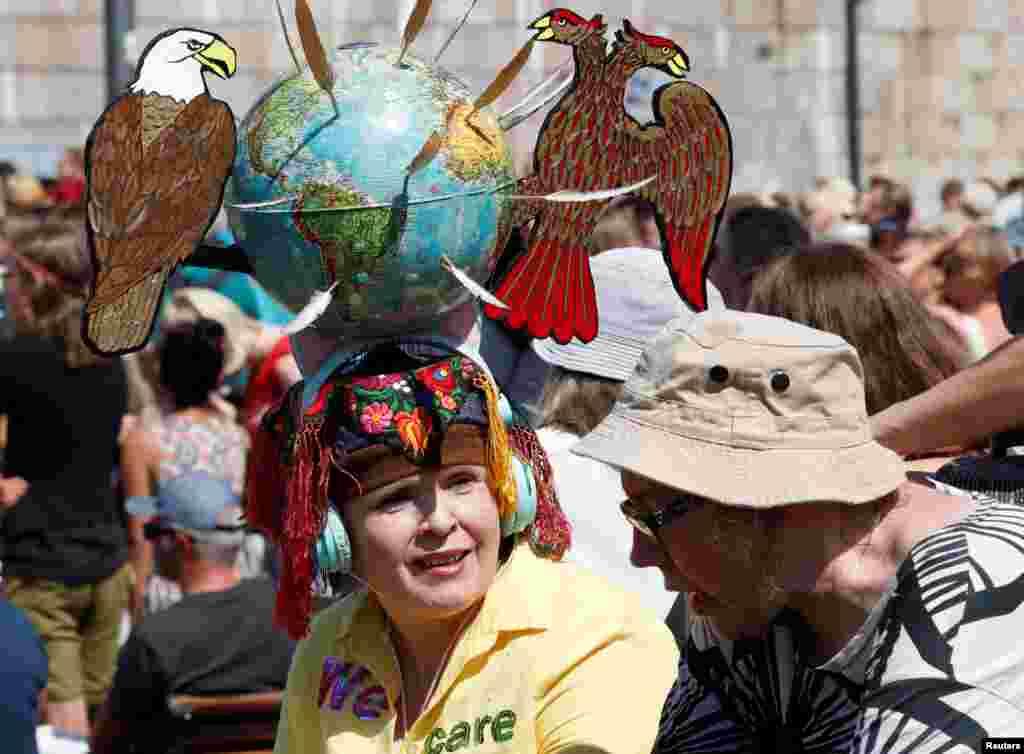 Женщина с инсталляцией на голове, где птичьи символы США – белоголовый орлан, и России – золотой двуглавый орел, своими перьями разметили земной шар между собой