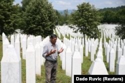 Ramiz Nukic prays near the graves of his father and two brothers in the Srebrenica-Potocari Memorial.