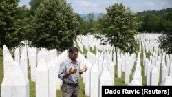 Рамиз Нукиќ се моли во близина на гробовите на неговиот татко и двајцата браќа во Меморијалот Сребреница - Поточари.