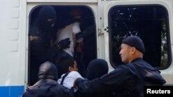 Сотрудники полицейского спецназа заталкивают в автобус задержанных во время сорванной властями акции протеста против земельной реформы. Алматы, 21 мая 2016 года.