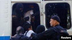 Сотрудники полиции заталкивают в автобус задержанных во время сорванной властями акции протеста против земельной реформы. Алматы, 21 мая 2016 года.