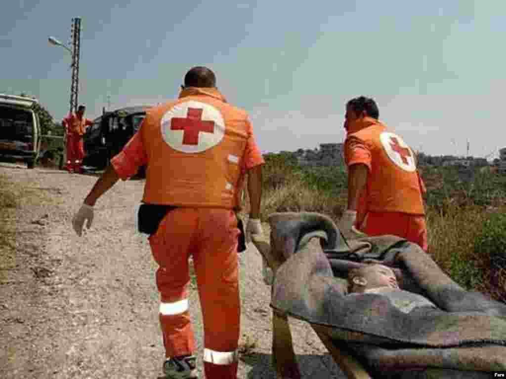 کارگران صلیب سرخ جسد کودکی را که در اثر حمله اسراییل به لبنان جان باخته است به آمبولانس منتقل می کنند