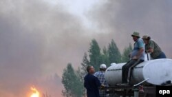 Local residents with a water tank watch as a fire approaches their village of Berestyanki, in the Ryazan region, on August 9.