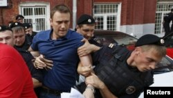 Policemen detained opposition leader and anticorruption blogger Aleksei Navalny (center) after he visited the city's election commission office on July 10 to submit documents to register as a mayoral election candidate in Moscow.