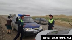 Полицейские на автодороге Актау — Каракия, задержавшие такси, где находилась корреспондент Азаттыка Сания Тойкен. 30 апреля 2016 года.