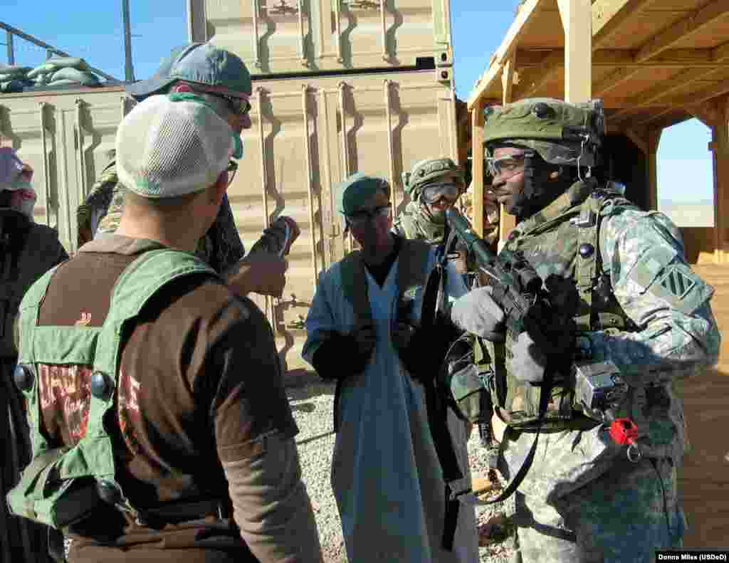 A member of the U.S. Army's 3rd Infantry Division interacting with soldiers posing as Iraqi citizens during a training exercise in Medina Wasl.