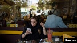 Iran -- An Iranian woman uses her mobile phone to follow election news in a coffee shop in Tehran, Iran May 17, 2017.
