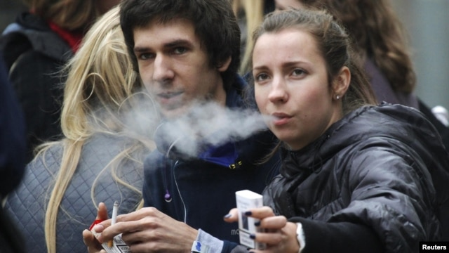 Russian students smoke on a street in Moscow
