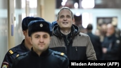 Dennis Christensen is escorted into the courtroom to hear his verdict in the town of Oryol on February 6.