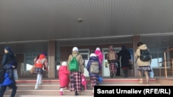 Ученицы в платках вместе с матерью на крыльце школы в Уральске. Иллюстративное фото.
