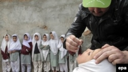 A health worker administers a polio vaccine to a child during a three-day nationwide vaccination campaign to eradicate polio in a heavily Afghan area of Islamabad, Pakistan, on January 21.