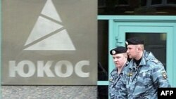 Two Russian policemen pass by the Yukos oil giant's logo during the controversial auctioning of some of the company's key assets at its headquarters in 2007. (file photo)