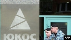 Russian police pass by the Yukos oil giant's logo during an auction selling off the company's key assets at its Moscow headquarters in May 2007.
