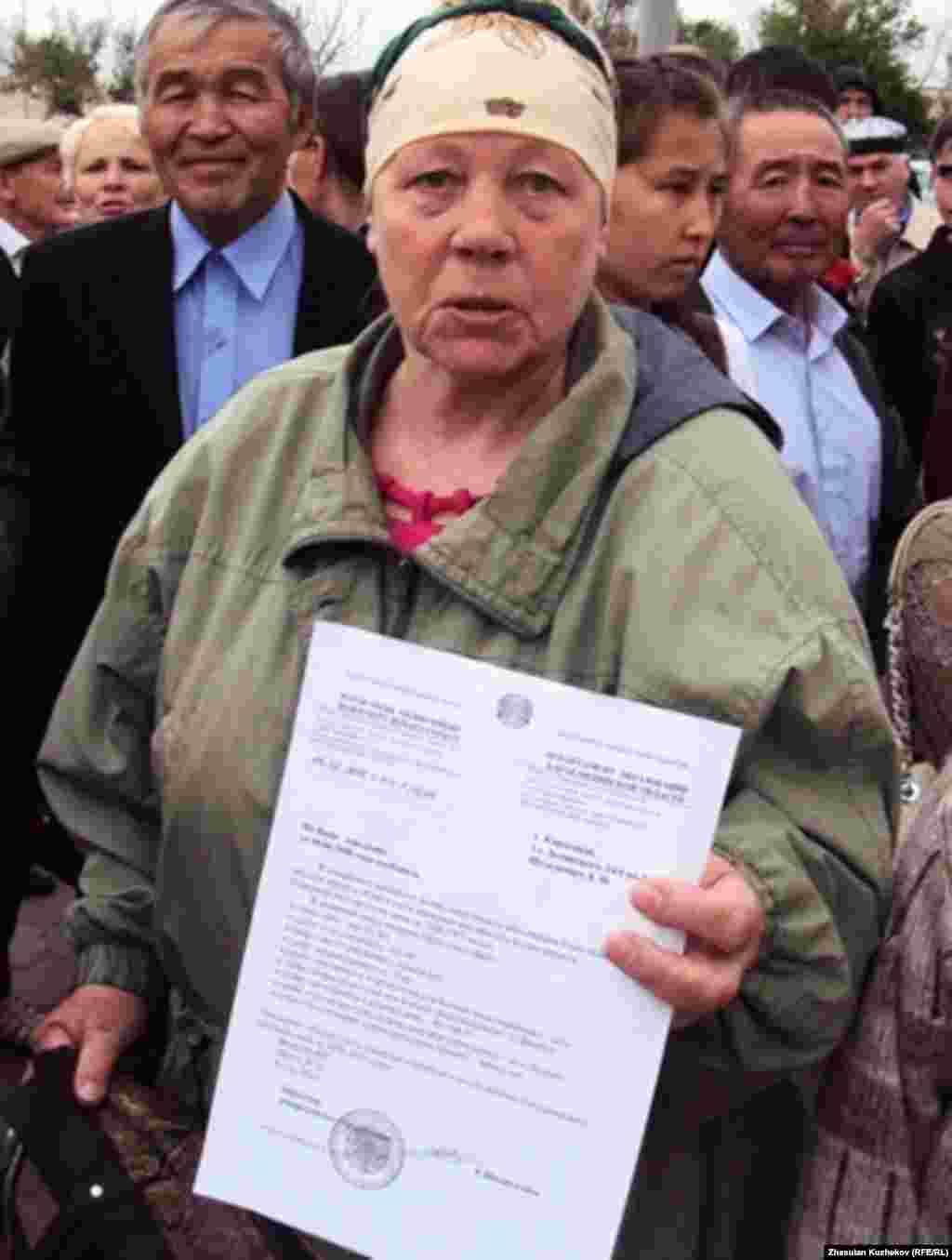 Бұрынғы Карлаг тұтқыны Лидия Шультевич өзінің ақталғаны туралы құжатты ұстап тұр. Қарағанды облысы Долинка ауылы, 31 мамыр, 2011 жыл.