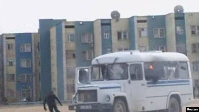 Kazakhstan -- A protester runs from a police vehicle on fire in the Kazakh town of Zhanaozen in this still image taken from video acquired by Reuters TV, 16Dec2011