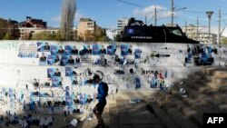 A man walks in front of a wall covered by electoral posters in the divided town of Mitrovica on November 4.