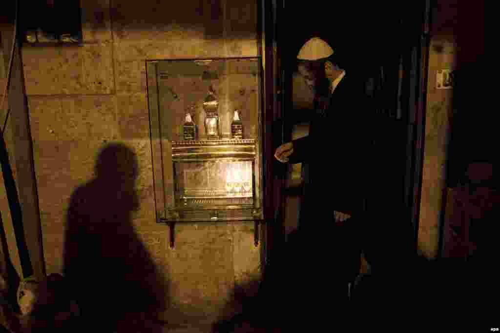 An Ultra-Orthodox Jew prays after lighting a candle outside his house during the Jewish holiday of Hanukkah in the Mea Shearim neighborhood of Jerusalem, Israel, on December 26. (epa/Abir Sultan)