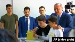 Президент Турции Реджеп Тайип Эрдоган со своими внуками на избирательном участке в Стамбуле, 24 июня 2018 года.
