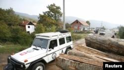 Vozilo KFOR-a porazi pored pomaknutih balvana na barikadi u selu Zupče, 27. oktobar 2011.