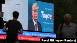 Interim Kazakh President Qasym-Zhomart Toqaev is seen on an electronic election billboard.