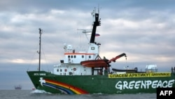 "Greenpeace's icebreaker ""Arctic Sunrise"" sails the Pechora Sea somewhere off Russia's northeastern coast with Gazprom's ""Prirazlomnaya"" Arctic oil platform in the background in a Greenpeace handout photo from September 17."