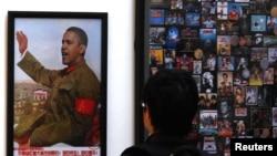 Көргөзмөдөгү Мао Цзэдундун портретине Барак Обаманын башы ширетилген сүрөттү бир көрүүчү тигиле кароодо. Бээжин, Кытай. 21.11.2011.