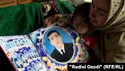 Вдова Сухроба Хушакова показывает фото своего супруга